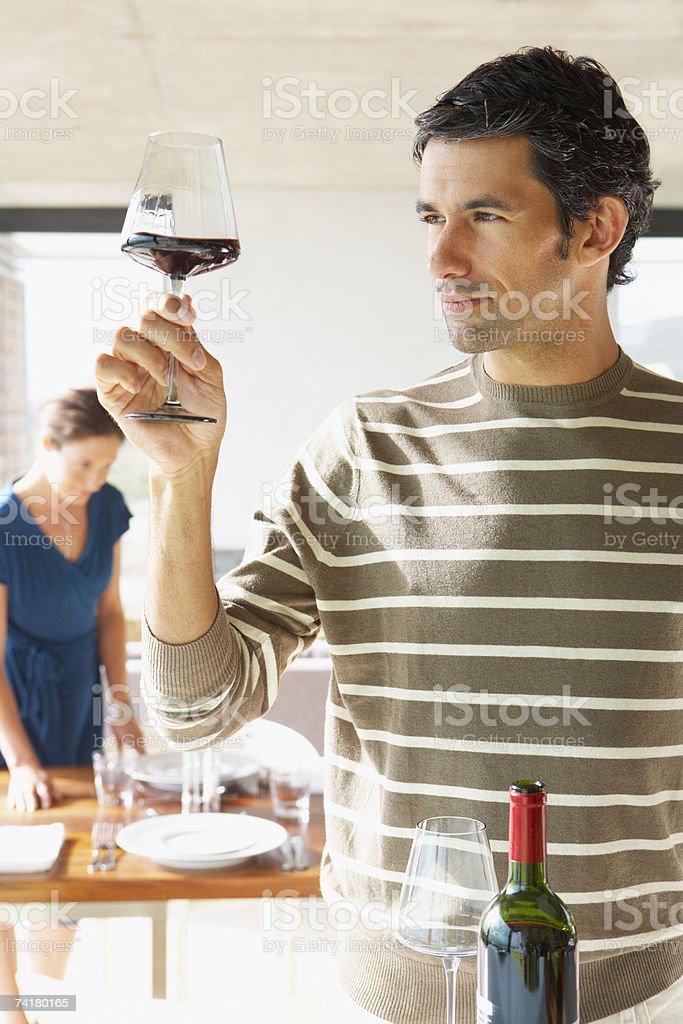 Homem com vinho tinto em vidro e mulher no fundo foto de stock royalty-free