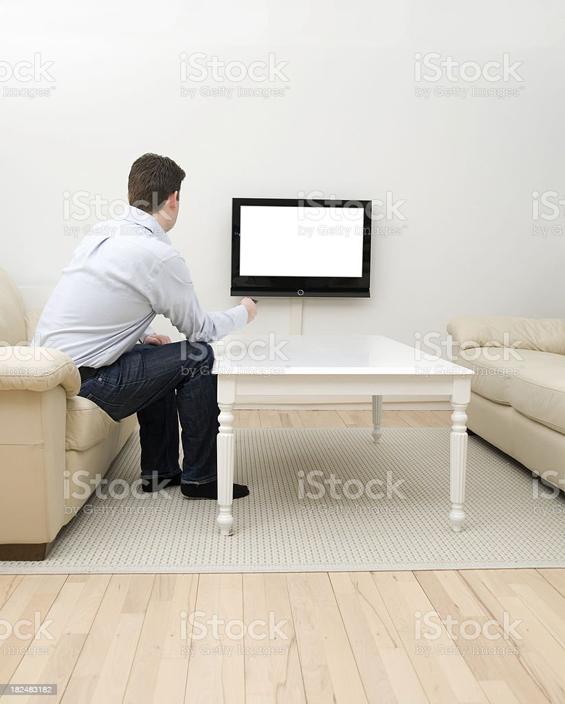 Man with remote control changes channel on flatscreen tv royalty-free stock photo