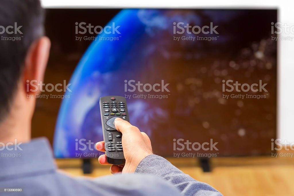 Man with remote control watching tv stock photo