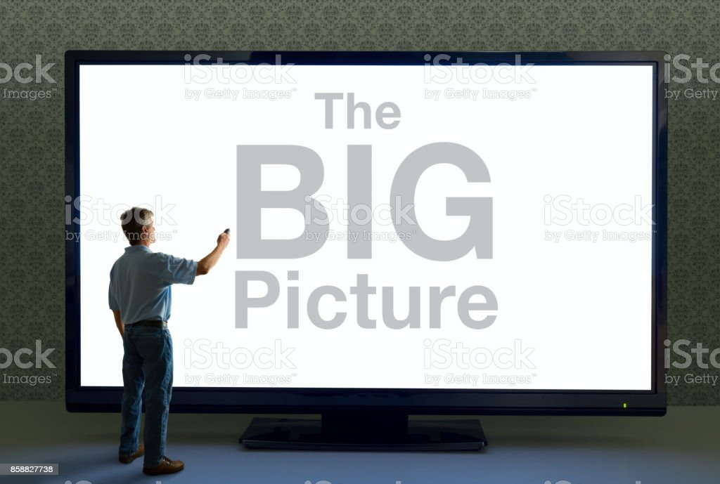 Man with remote pointing it at giant television that says The BIG Picture stock photo