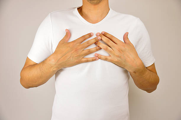 man with respiration problems man with both hands on breast because of hard breathing and angina pectoris on grey background breast stock pictures, royalty-free photos & images