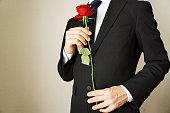 バラの花を持つ男。