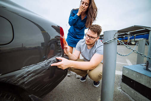 istock man with sad look on scratched car. woman with sorry look near d 941132212