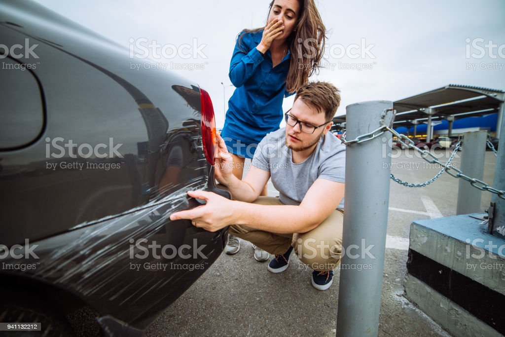 man with sad look on scratched car. woman with sorry look near d stock photo