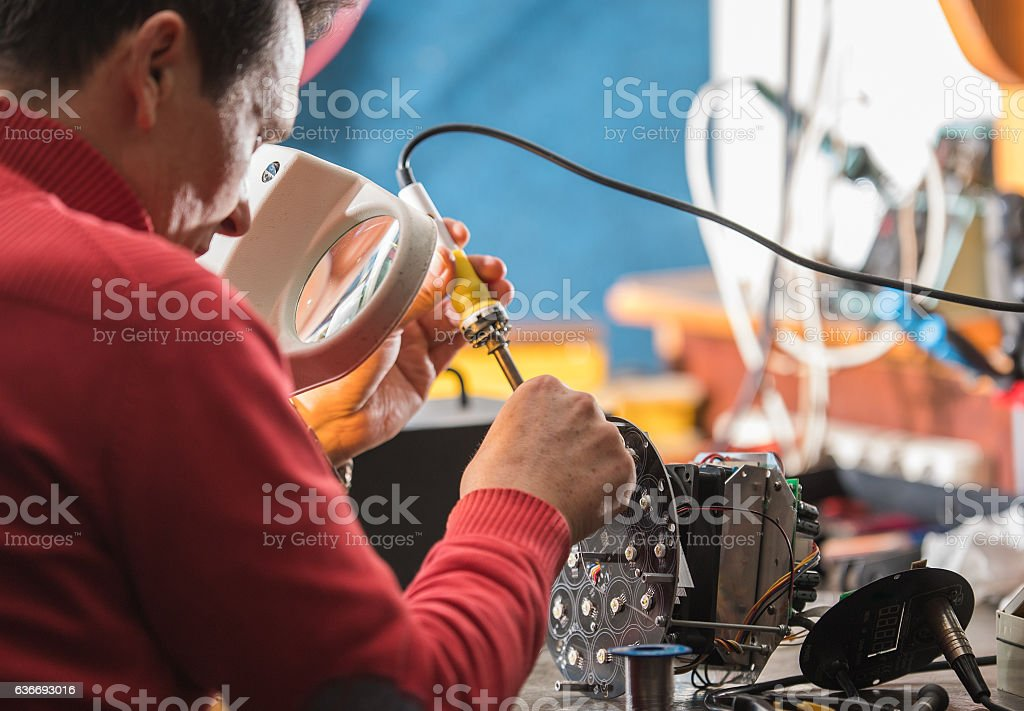 Man with safety glasses repairing motheboard with soldering iron stock photo