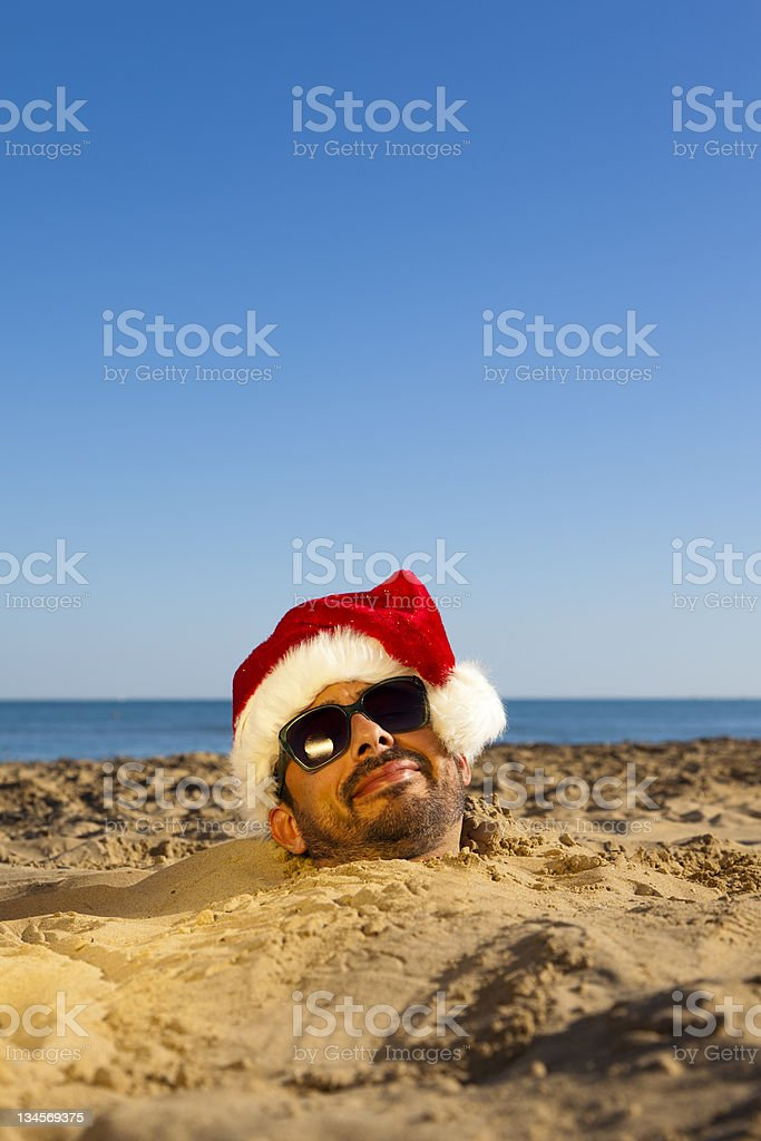 Man with Santa Claus hat during christmas time on a tropical beach....
