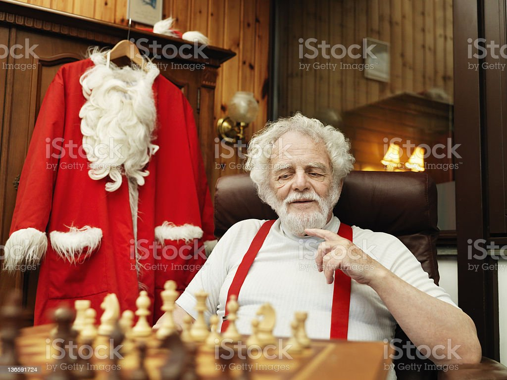 Man with Santa Claus suit playing chess royalty-free stock photo