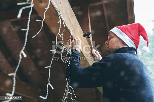 man with santa hat decorating house outdoor carport with christmas string lights