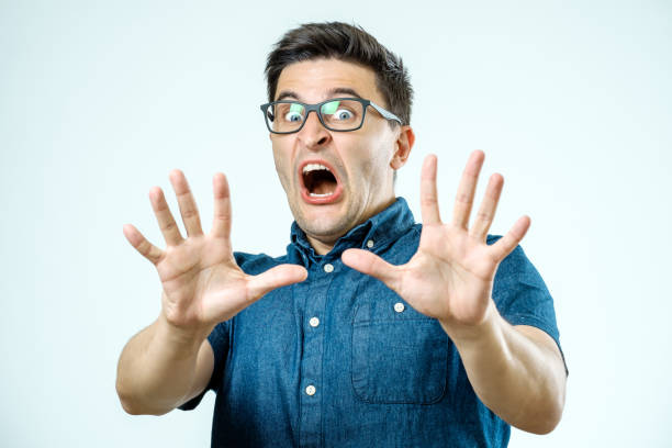 Man with scared expression on his face making frightened gesture with his palms as if trying to defend himself from someone stock photo
