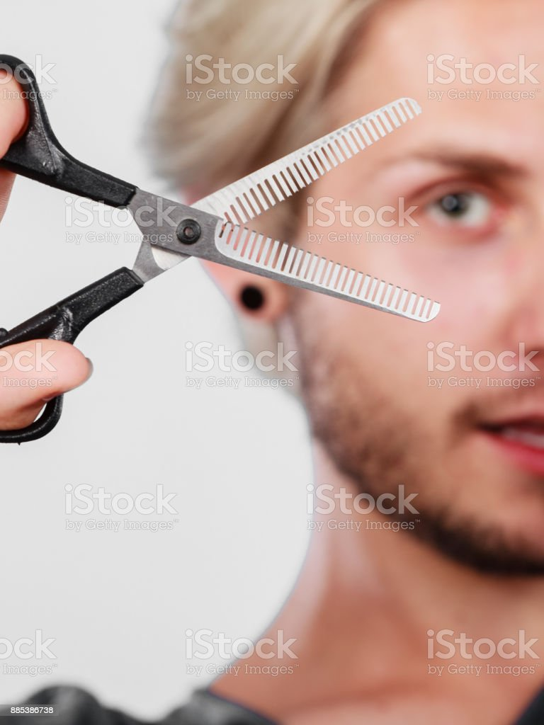 Man with scissors texturizing or thinning shears stock photo