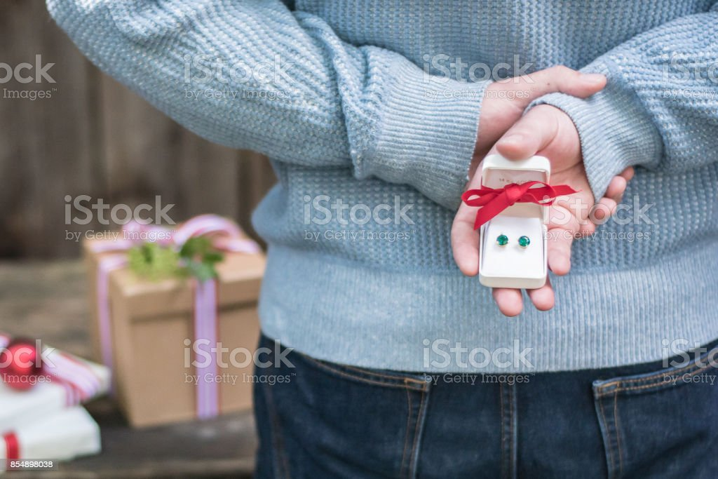 young man holding surprise christmas gifts behind his back in a...