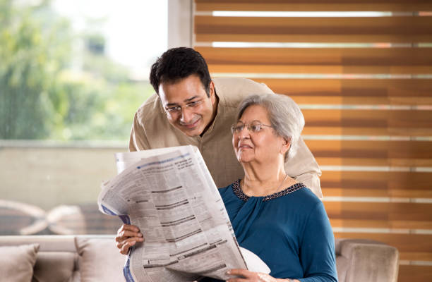Man with senior mother at home Man spending time with senior mother reading newspaper at home old mother son asian stock pictures, royalty-free photos & images