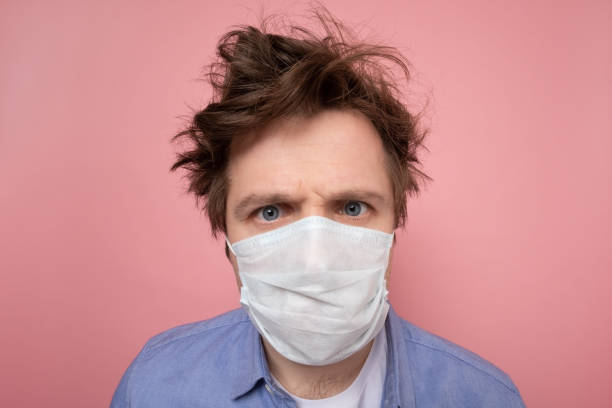 man with shaggy hairstyle and medical mask. I urgently need a hairdresser stock photo