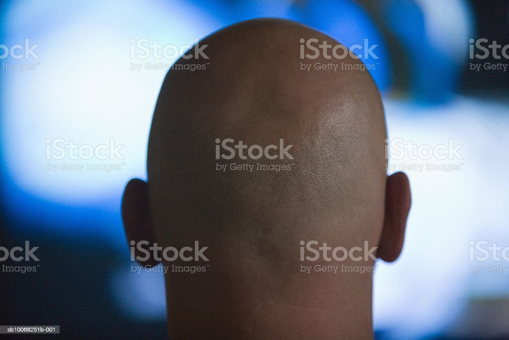 Man with shaved head watching tv, rear view royalty-free stock photo