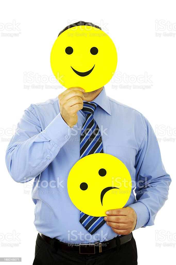 Man with shirt and tie holding smiley face and sad face stock photo
