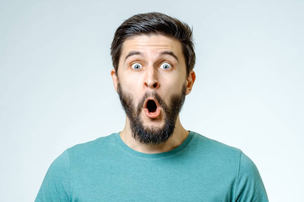 man with shocked, amazed expression isolated on gray background - sorpresa foto e immagini stock