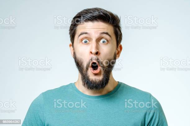 Man with shocked, amazed expression isolated on gray background