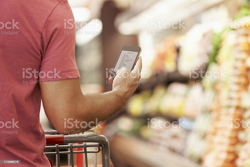 Man with shopping cart reads from cell phone stock photo