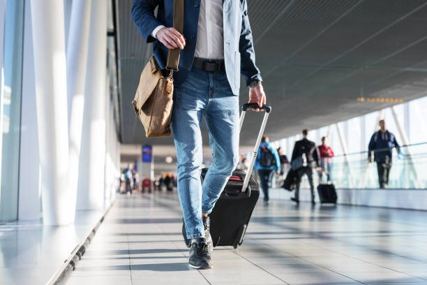Man with shoulder bag and hand luggage walking in airport terminal stock photo