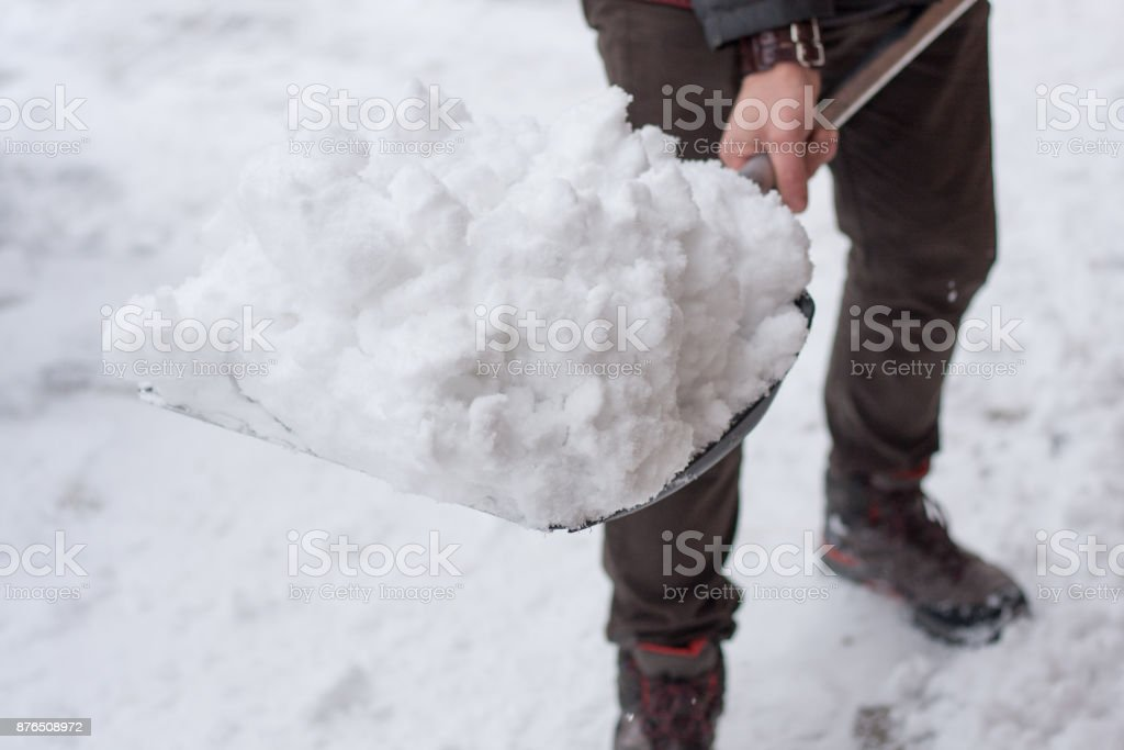 Man with shovel cleaning snow filled backyard outside his house. royalty-free stock photo