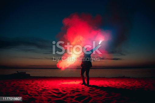 Man sends signal with colorful fire or fireworks in hands at sunset beach