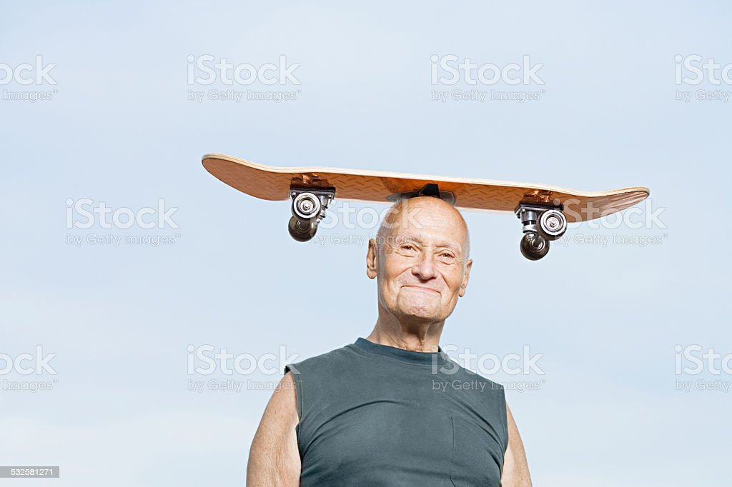 Man with skateboard on his head stock photo