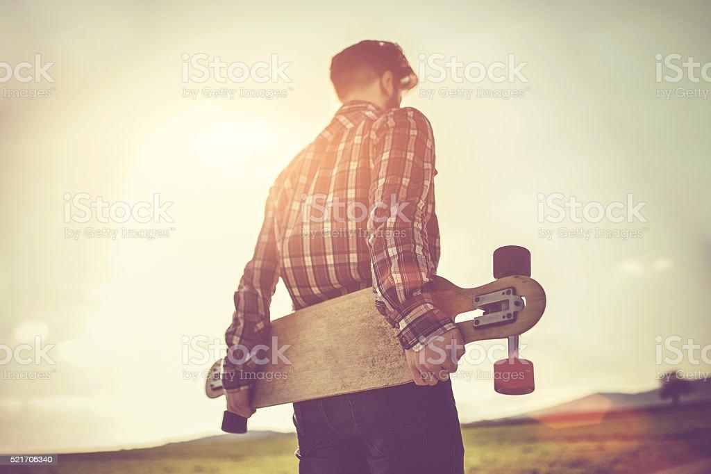 Man with skateboard under the sun stock photo
