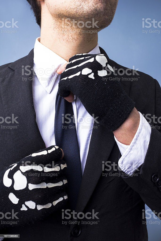 Man with skeleton gloves adjusting his tie royalty-free stock photo