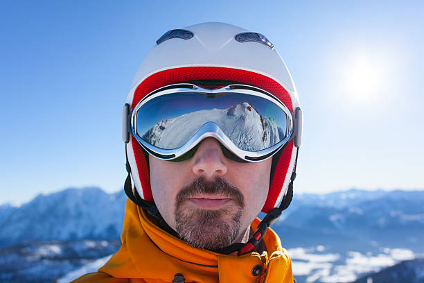 man with skiing goggles and reflections face of skier wearing a skiing helmet and goggles with reflections ski goggles stock pictures, royalty-free photos & images