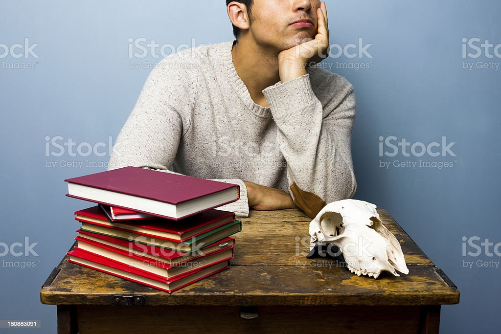 Man with skull and books is trying to think royalty-free stock photo