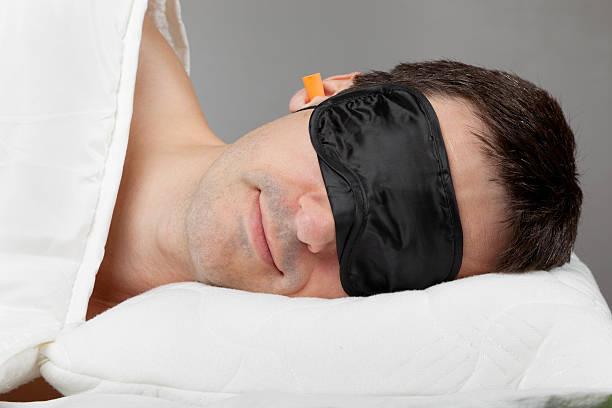 man with sleeping mask and earplugs in bed - blindfolded headphones bildbanksfoton och bilder