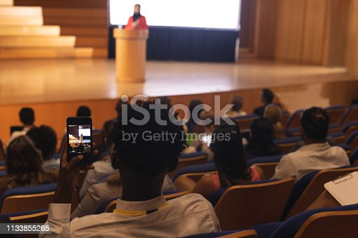 1133856033 istock photo Man with smartphone taking video clip of businesswoman in the auditorium 1133855265