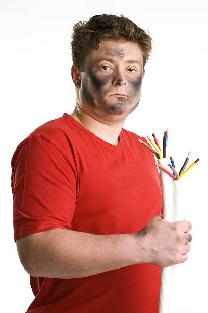 Man with smoked black face holds two cable. stock photo