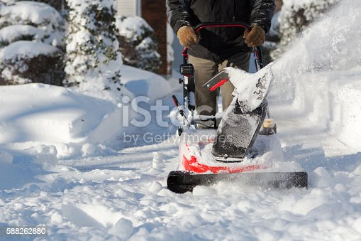 unrecognizable man clearing snow from walkway in front of house with a snowblower machine in winter