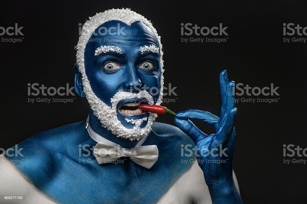 Man with snowy hair and beard eating chili pepper stock photo