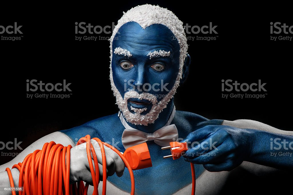 Man with snowy hair and beard holds power cord plug stock photo