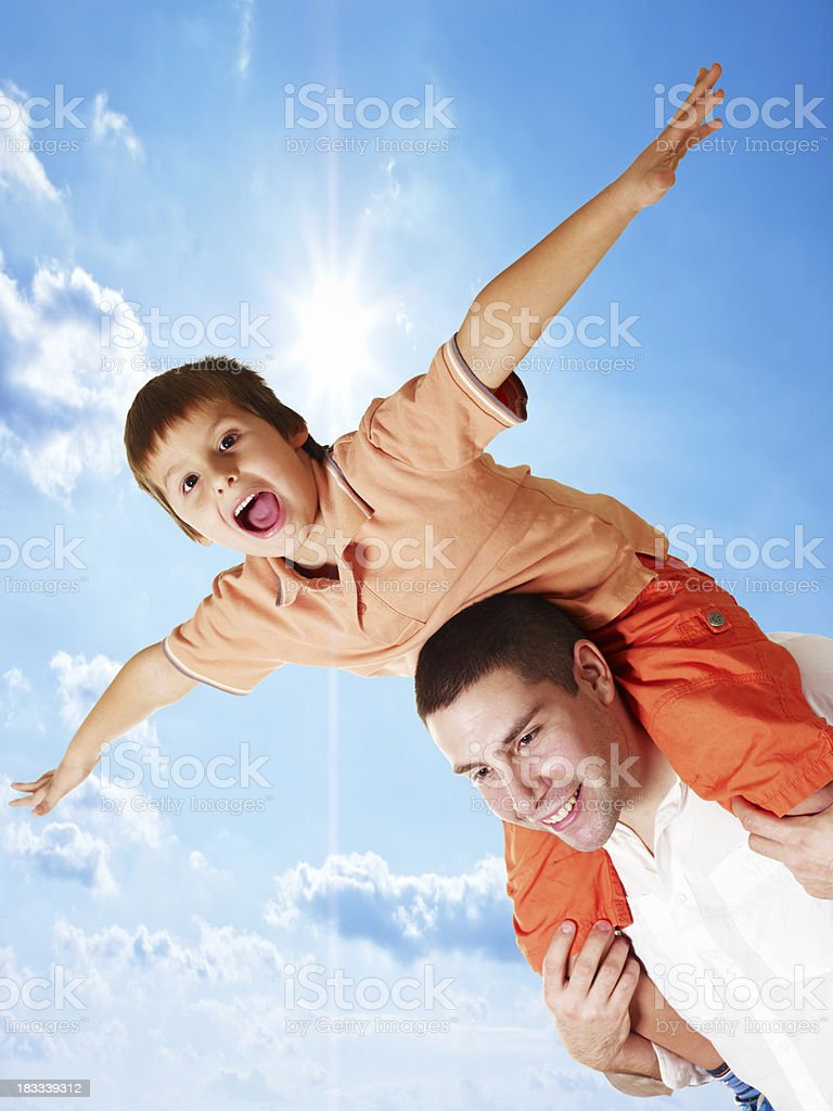 Man with son on back flying against sky royalty-free stock photo