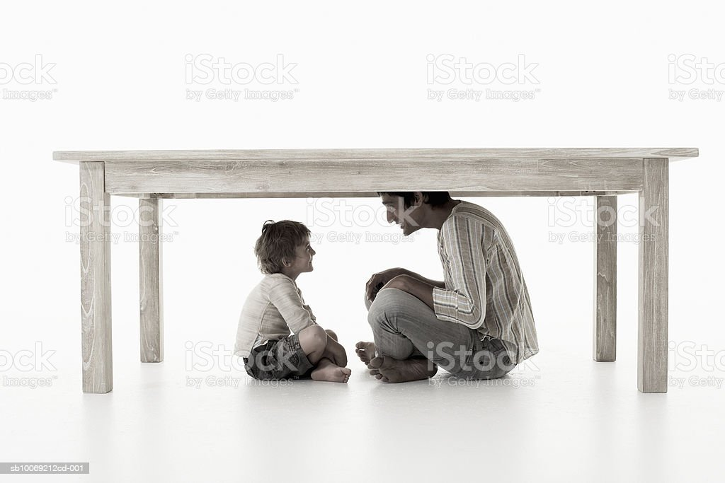 Man with son (4-5 years) sitting under table, studio shot royalty free stockfoto