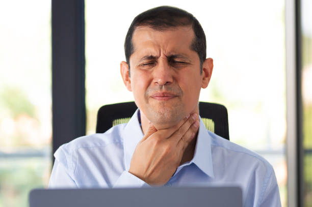 man with sore throat at the office Shot of a young businessman experiencing throat pain while working in an office heartburn throat pain stock pictures, royalty-free photos & images