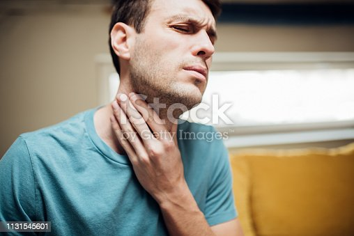Young man feeling pain in his throat