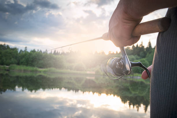 A man with spinning in the morning twilight on the river Bank. A man with spinning in the morning twilight on the river Bank. fishing reel stock pictures, royalty-free photos & images