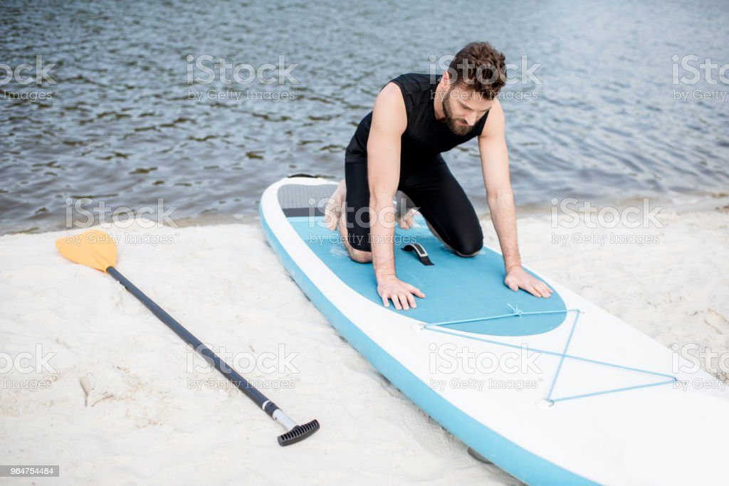 Man with standup paddleboard on the beach royalty-free stock photo