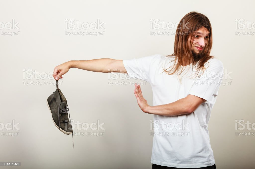 Man with stinky shoe stock photo