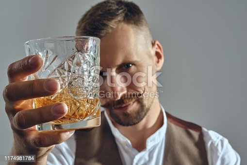 Bearded good-looking man with a stylish mustache, dressed in a classic brown vest and white shirt is sitting at the table, enjoying whiskey and raising a toast to you. Grey background, close-up shot.