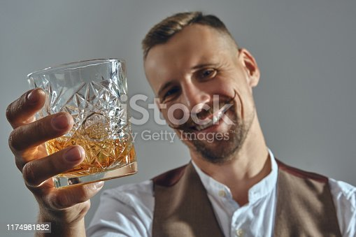 Bearded good-looking guy with a stylish mustache, dressed in a classic brown vest and white shirt is sitting at the table, enjoying whiskey, smiling and raising a toast to you. Grey background, close-up shot.