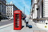 London, UK - May 15, 2019: Man with suitcase besides traditional red telephone box in London, England