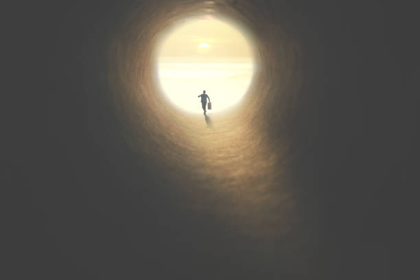 man with suitcase running to the exit of a tunnel illuminated of the sun stock photo