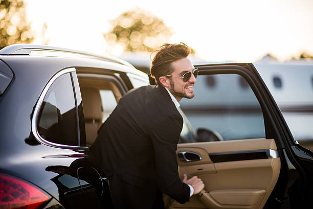 Man with sunglasses exits the black car stock photo
