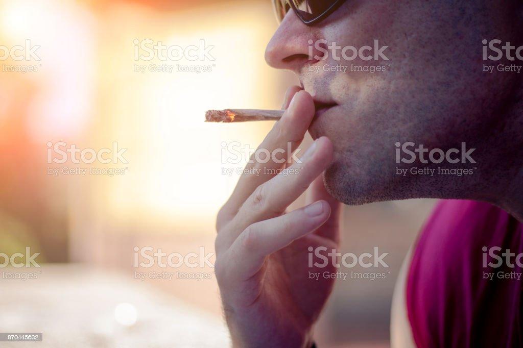 Man with sunglasses smoking marijuana cigarette outside on sunset stock photo