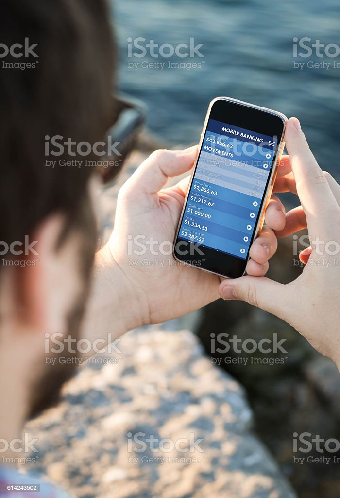 Man with sunglasses using the smartphone with mobile banking nea - foto stock